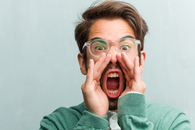 Junge hübsche unternehmermann-gesichtsnahaufnahme, die glücklich, überrascht durch ein angebot oder eine förderung schreit