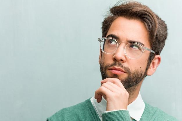 Junge hübsche unternehmermann-gesichtsnahaufnahme, die oben, verwirrt über eine identifikation denkt und schaut