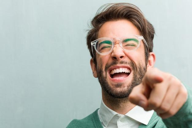 Junge hübsche unternehmermann-gesichtsnahaufnahme, die über anderen schreit, lacht und sich lustig macht