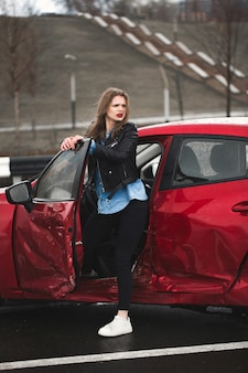 Junge hübsche verängstigte frau im auto. verletzte frau, die sich nach einem autounfall schlecht fühlt