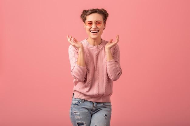 Junge hübsche verlassene lachende frau im rosa pullover und in der sonnenbrille lokalisiert auf rosa studiohintergrund