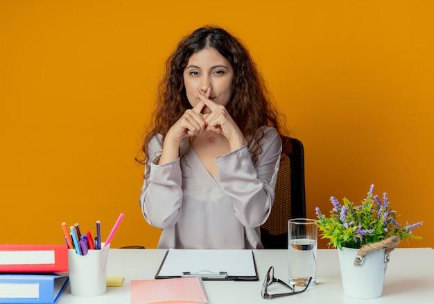 Junge hübsche weibliche büroangestellte, die am schreibtisch mit bürowerkzeugen sitzt, die geste nicht isoliert auf orange wand zeigen