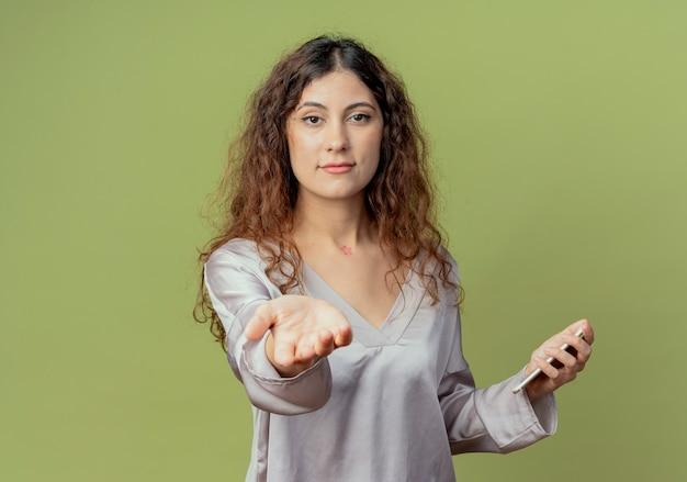 Junge hübsche weibliche büroangestellte, die telefon hält und hand lokalisiert auf olivgrüner wand heraushält