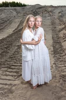 Junge hübsche zwillinge mit langen blonden haaren halten hände am sandsteinbruch in elegantem weißem kleid, rock, jacke
