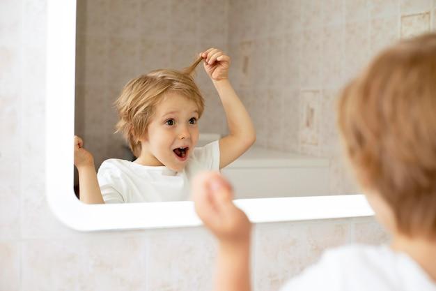 Junge im badezimmer, der im spiegel schaut