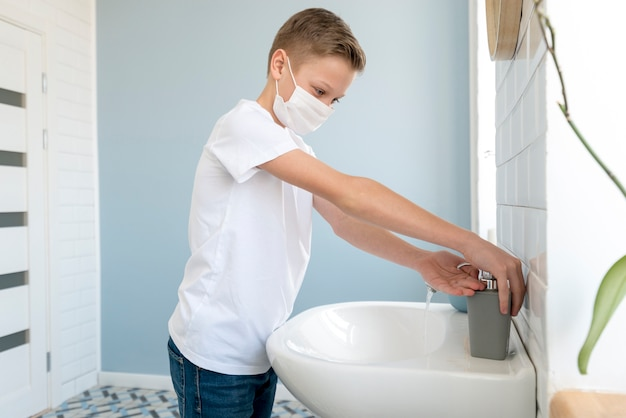 Junge im badezimmer, der medizinische maske trägt