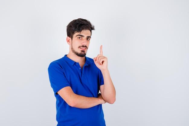 Junge im blauen t-shirt, der den zeigefinger in der heureka-geste anhebt und vernünftig aussieht, vorderansicht.
