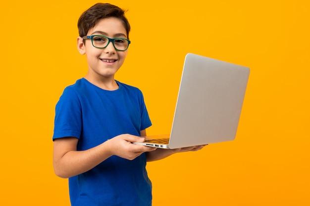 Junge im blauen t-shirt tippt auf laptop auf gelb