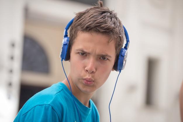 Junge im blauen t-shirt und in den blauen kopfhörern
