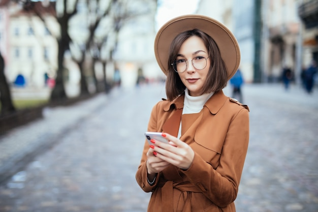 Junge im braunen mantel, der sms auf smartphone-herbststraße schreibt