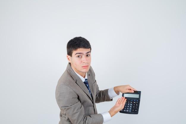 Junge im formellen anzug hält taschenrechner, zeigt darauf und sieht fröhlich aus, vorderansicht.