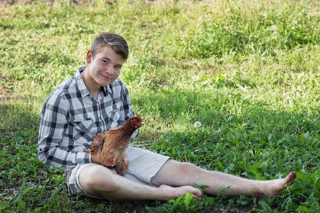 Junge im gras, das mit huhn spielt