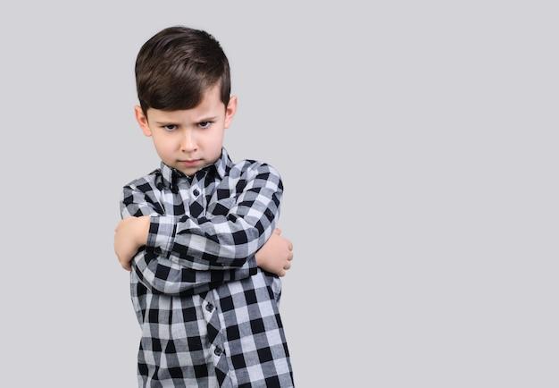 Junge im grauen hemd ist wütend auf studio grau isolierten hintergrund. der junge ist beleidigt