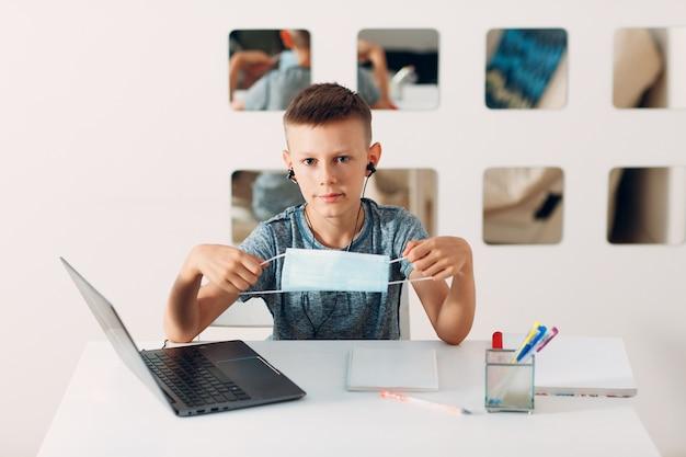 Junge im headset sitzt am tisch mit laptop und medizinischer gesichtsmaske und bereitet sich auf die schule vor