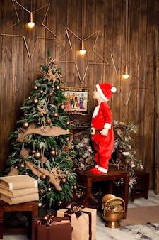 Junge im hellen schlafzimmer mit winterdekoration und weihnachtsbaum.