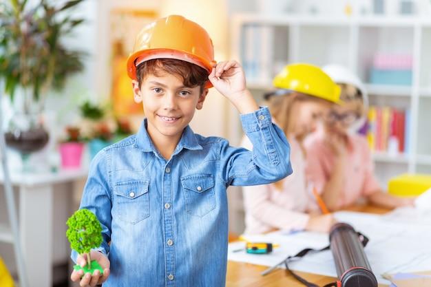 Junge im helm. junge trägt jeanshemd und helm lächelnd beim studium der hausmodellierung