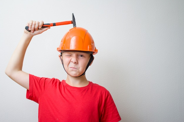 Junge im helm, schutzhelm. junger erbauer mit hocked gesicht klopft mit hammer auf kopf