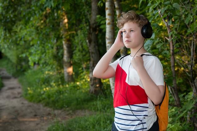 Junge im kopfhörer hört musik. jugendlicher in den kopfhörern im wald
