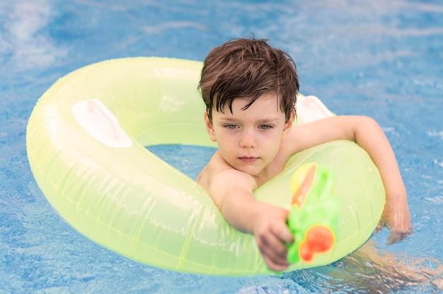 Junge im pool mit schwimmer