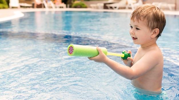 Junge im pool spielt mit wasserpistole