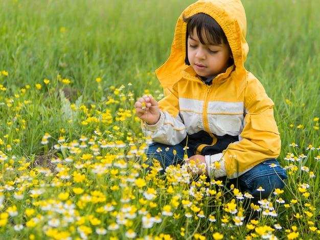 Junge im regenmantel, der blumen pflückt