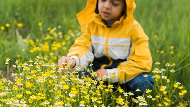 Junge im regenmantel, der blumen vorderansicht pflückt