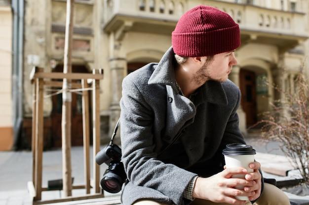 Junge im roten hut sitzt durchdacht auf der bank mit tasse kaffee in seinen armen