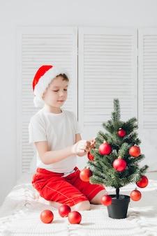 Junge im roten sankt-hut verziert kleine christbaumkugeln