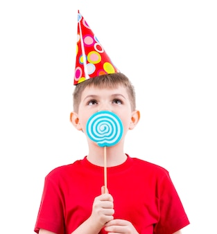 Junge im roten t-shirt und im partyhut, die farbige süßigkeiten essen - lokalisiert auf weiß.
