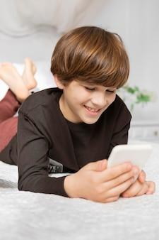Junge im schlafzimmer mit telefon