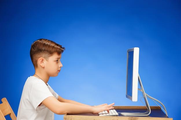 Junge im schulpflichtigen alter sitzt vor dem monitor-laptop