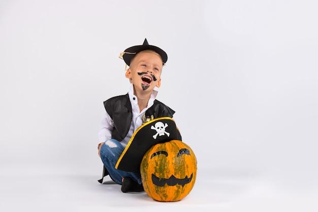 Junge im schwarzen handgemachten hut. in der nähe ist kürbis in piratenhut. beide sind schrecklich gemalt.