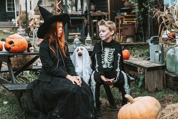 Junge im skelettkostüm und mädchen in einem hexenkostüm mit einem hund in einem geisterkostüm halloween party