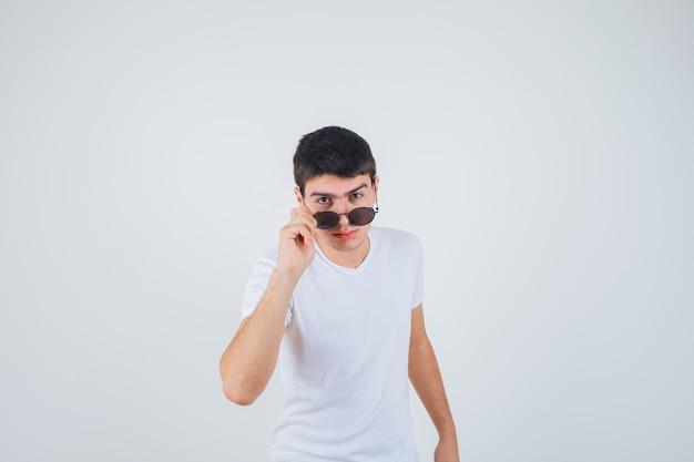 Junge im t-shirt, das brille hält, kamera betrachtet und cool, vorderansicht schaut.