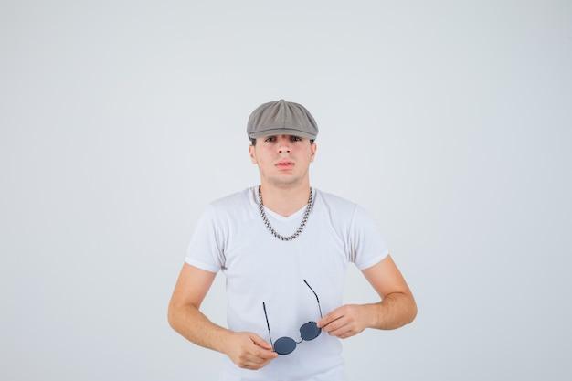 Junge im t-shirt, hut, der brille hält, kamera betrachtet und zuversichtlich schaut, vorderansicht.