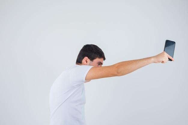 Junge im t-shirt werfen handy weg und schauen zuversichtlich, vorderansicht.