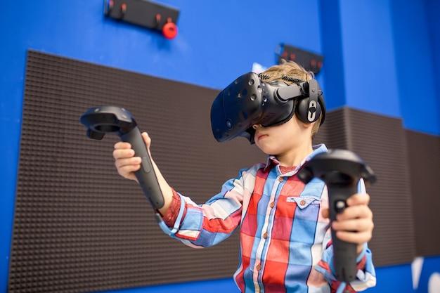 Junge im virtual-reality-headset spielt videospiel im game center