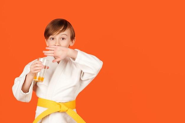 Junge im weißen kimono trinkt wasser kind, das karate auf farbigem hintergrund übt kindersportkonzept
