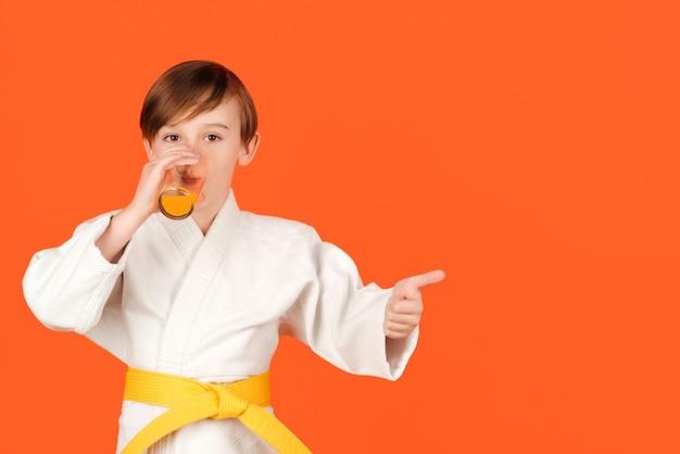 Junge im weißen kimono trinkt wasser. kind, das karate auf farbigem hintergrund übt. kindersportkonzept.