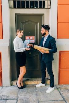 Junge immobilienmakler verkaufen eine immobilie