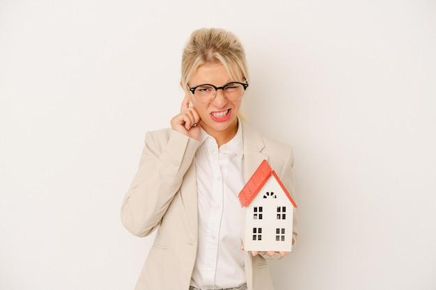 Junge immobilienmaklerfrau, die ein hausmodell lokalisiert auf weißem hintergrund hält, der ohren mit den händen bedeckt.