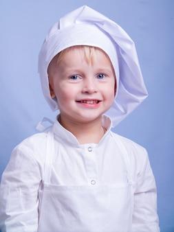 Junge in anzug und kochmütze lächelt