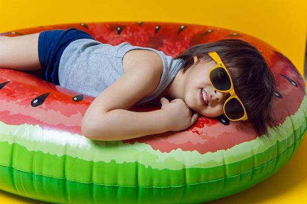 Junge in blauen badehosen und sonnenbrillen, die auf einem aufblasbaren kreis in form einer wassermelone auf einer gelben wand liegen