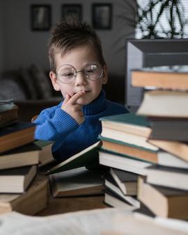 Junge in brille liest ein buch mit einem stapel bücher neben sich.