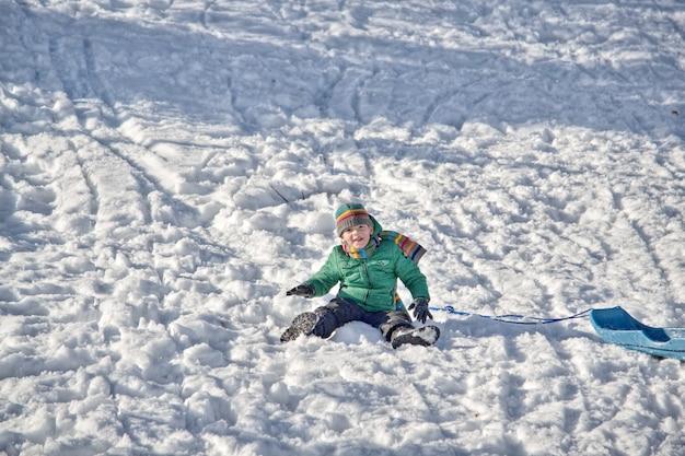 Junge in den bergen reitet im schnee auf einem schlitten