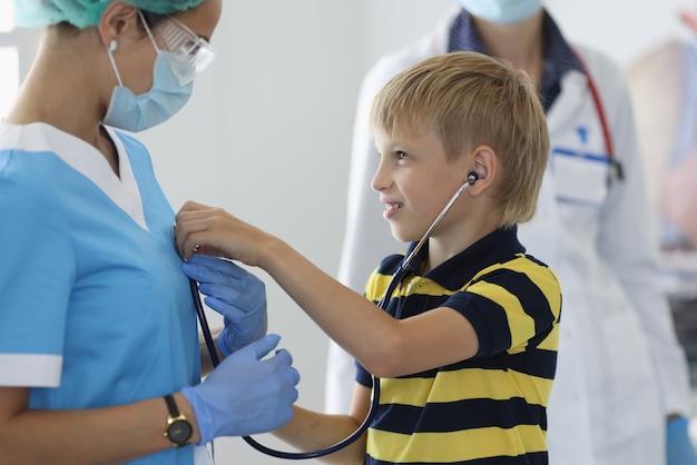 Junge in der arztpraxis hört durch stethoskop auf den atem des arztes