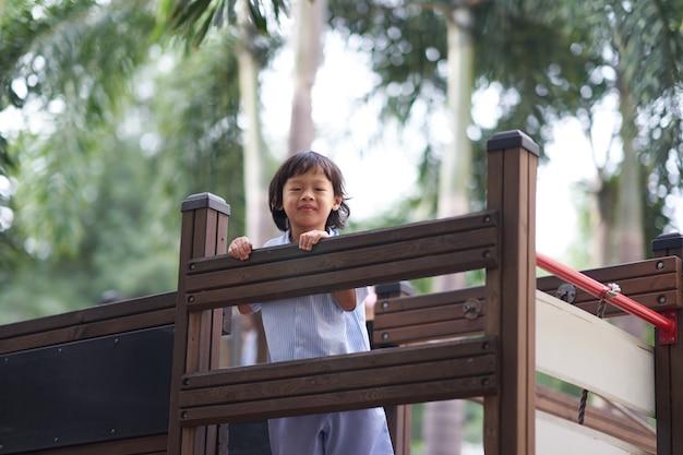 Junge in der einheitlichen schule, die im spielplatz spielt