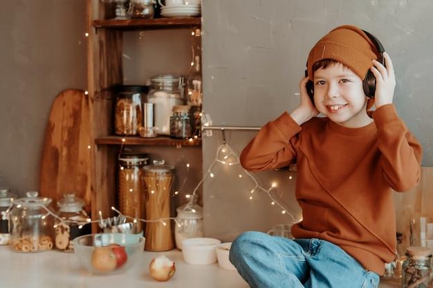 Junge in der küche, der musik durch drahtlose kopfhörer hört.