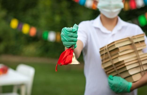 Junge in der medizinischen maske und in den handschuhen, die bücher und goldene schulglocke halten