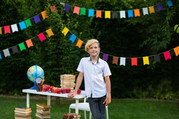 Junge in der schuluniform, die nahe weißem schreibtisch aufwirft, initiiert den hinterhof.